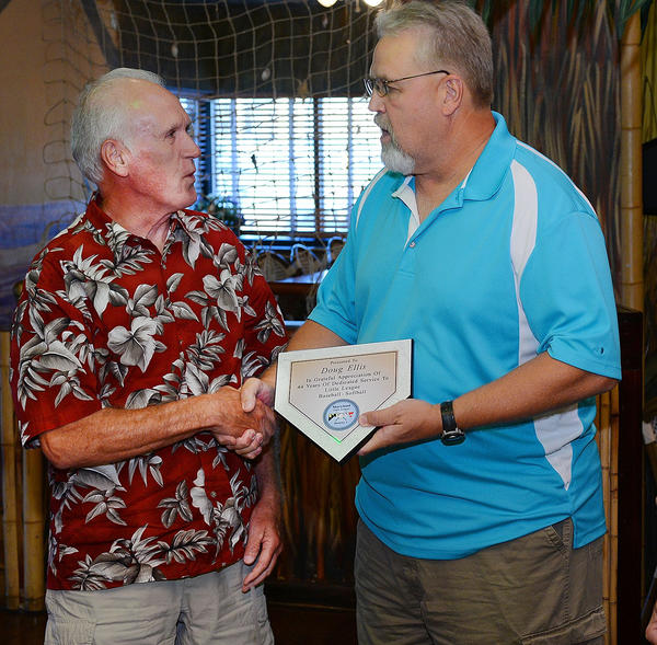 Doug Ellis, left, is congratulated by Larry Hammond, District 1 Administrator after Elllis was given a plaque for his years of service to the LIttle League District.