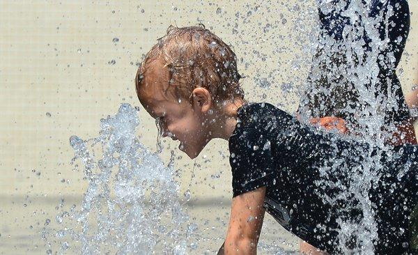 A child cools off Thursday while playing in the fountains at California Plaza in downtown Los Angeles.