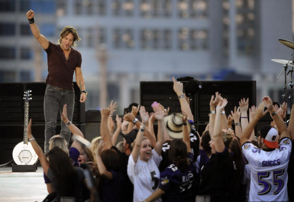 Country star Keith Urban greets the crowd at the beginning of his NFL Kickoff concert at the Inner Harbor Thursday night.