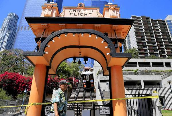 Pedestrians stroll past Angels Flight in downtown Los Angeles after one of the cars came off the track because of a power disruption. An Australian tourist was stranded, but nobody was injured. Five passengers on the funicular's other car were also assisted off.