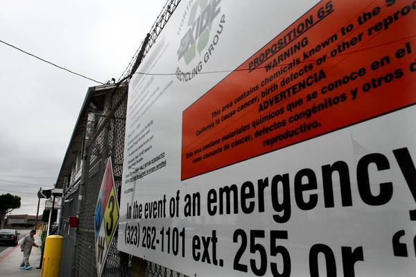 The latest report comes after a health-risk report released in the spring showed elevated arsenic emissions from the plant were posing an increased cancer risk to more than 110,000 people. Above, an employee wearing protective coverings on his shoes walks into Exide.