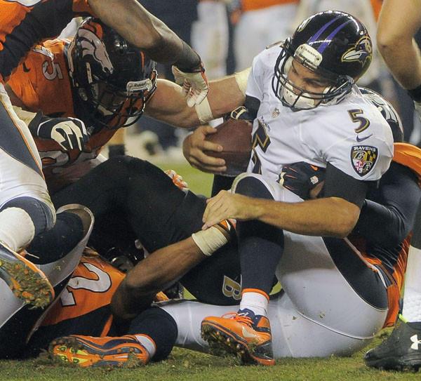 Joe Flacco is sacked by a host of Broncos defenders.