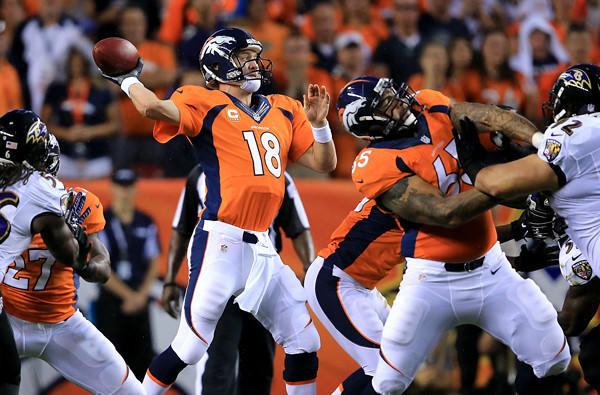 Broncos quarterback Peyton Manning (19) fires a pass against a strong rush by the Ravens during their season-opening game Thursday night in Denver.