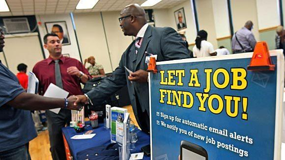 Job seekers speak with an employer at an Illinois Department of Employment Security job fair in Chicago in July.