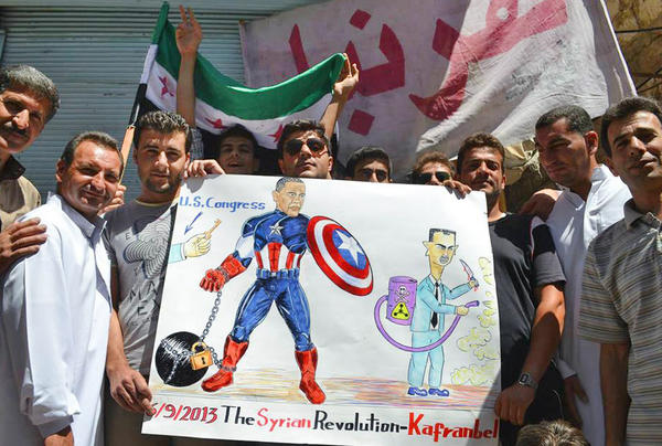 An image provided by Edlib News Network and authenticated by the Associated Press shows protesters opposed to the Syrian government holding a poster depicting President Obama and Syrian President Bashar Assad during a demonstration in Kafr Nabil, Syria.