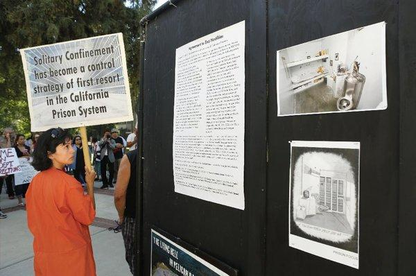 Diya Malika, of the Stop Mass Incarceration Network, glances at some information about the secure housing units in California prisons, during a rally calling for the end of solitary confinement in California prison, on Aug. 14 at the Capitol in Sacramento.