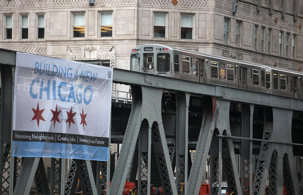 A CTA train crosses the Wells Street Bridge near the Merchandise Mart in the Loop.
