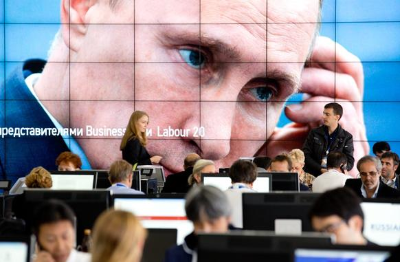 The eyes of Russia's President Vladimir Putin peer out from a giant screen in the media center at the G20 summit in St. Petersburg.