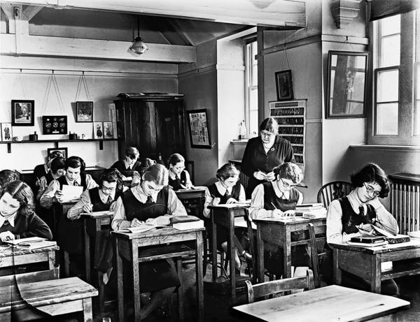 Girls in the upper fourth form of the girl's School at Christ's Hospital, Hertford, are given a history lesson by the author of their new history text book, Miss F M Page.
