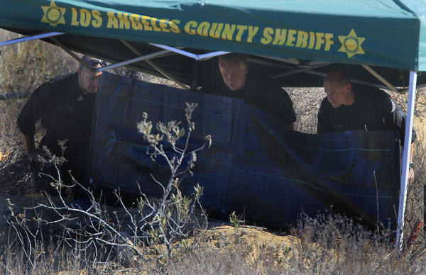Investigators from the Los Angeles County Sheriff's Department study the scene off Lake Hughes Road in Castaic where a burnt body was discovered early Wednesday morning.