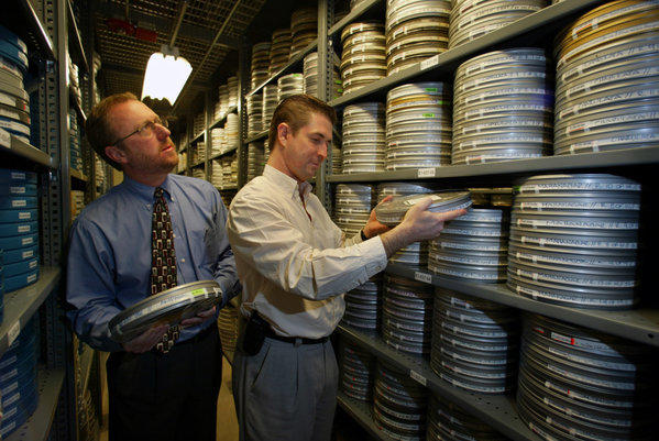 Ric Robertson, left, in the Academy Film Archive with a fellow academy employee. Robertson will step down from his role as COO, effective immediately.