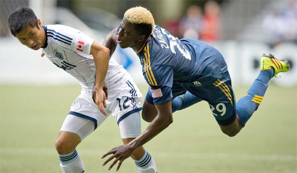 Forward Gyasi Zardes is sent flying after a collision with defender Lee Young-Pyo during the first half of the Galaxy's win over the Vancouver Whitecaps FC, 1-0, on Aug. 24, 2013.