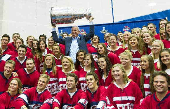 Saint Mary's University alumnus John McDonough, the president and CEO of the Blackhawks, holds up the Stanley Cup while taking photos with the SMU men's and women's hockey teams at SMU's Gostomski Fieldhouse in Win