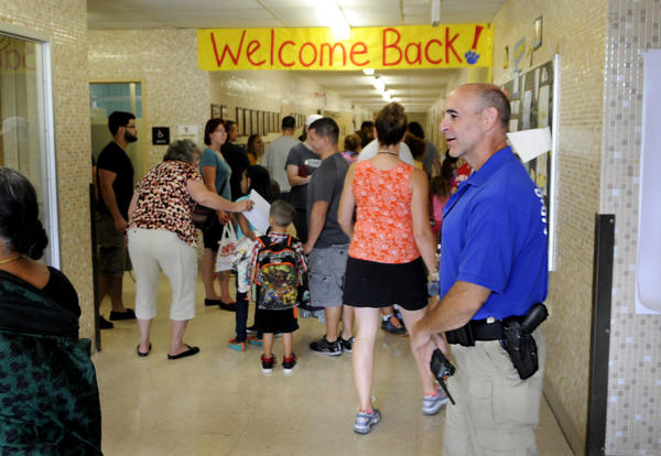 It was opening day for the Henry Barnard Elementary School. Looking on, at right, is the school's armed security guard, Kevin Hart, a 21-year veteran with the Hartford Police Deptartment and now retired. This is the first year that armed guards have been stationed at all of Enfield's public schools. The K-2 school has 347 students.