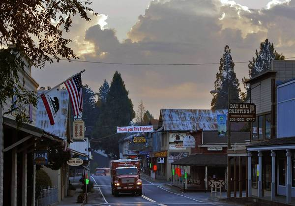 "California Department of Forestry crew trucks move through Groveland last week at dawn under a banner that reads ""Thank you Fire Fighters"" on California 120."