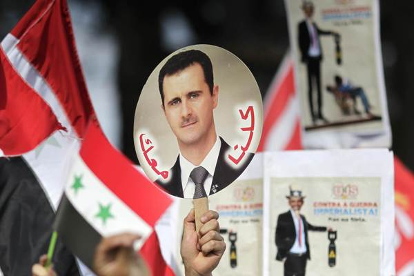 Students hold a sign with a picture of Syria's President Bashar al-Assad during a protest by a students' national union against possible U.S. military action in Syria, in Brasilia September 6, 2013.