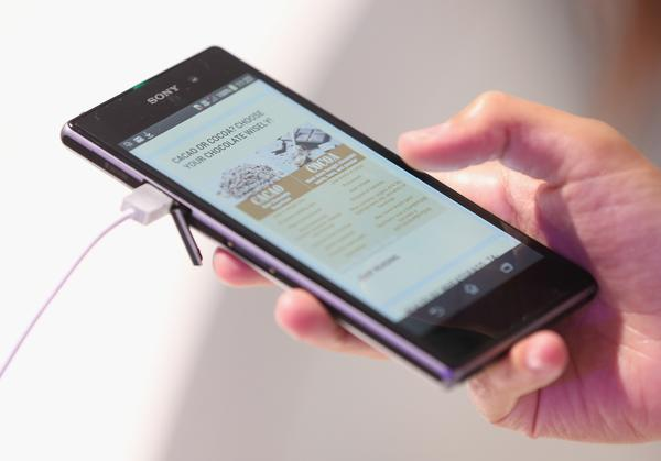 A visitor tries out an Xperia Z1 smartphone at the Sony stand at the IFA 2013 consumer electronics trade fair in Berlin, Germany.