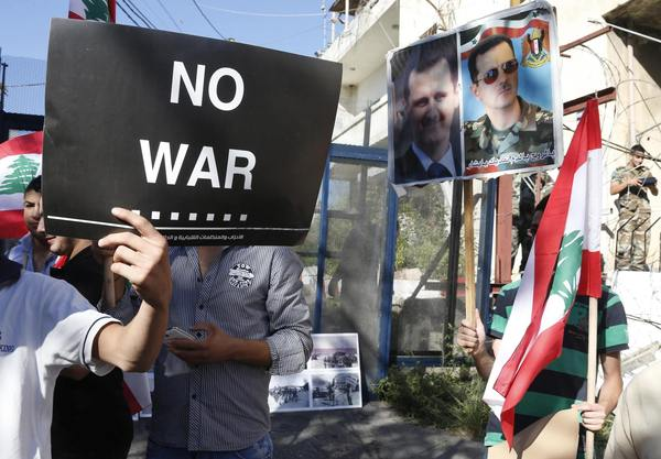 Activists hold banners, Lebanese flags and pictures of Syria's President Bashar al-Assad during a sit-in near the U.S. embassy in Awkar, north of Beirut, against potential U.S. strikes on Syria September 6, 2013.