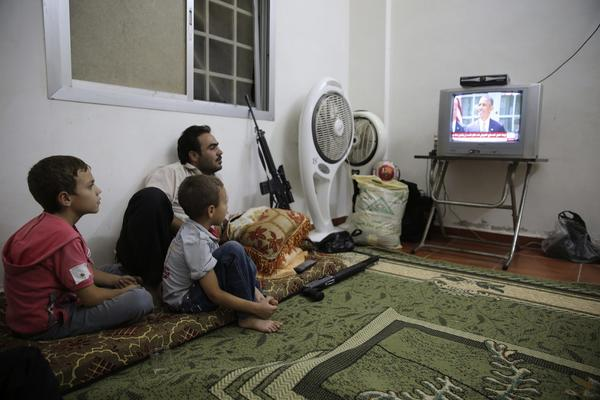 A Free Syrian Army fighter watches President Barack Obama's speech with his family in Ghouta, Damascus August 31, 2013.