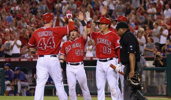 Mark Trumbo, left, is congratulated by teammates Kole Calhoun, center, and Hank Conger after hitting a three-run home run during the fourth inning of the Angels' 6-5 win over the Texas Rangers on Friday.