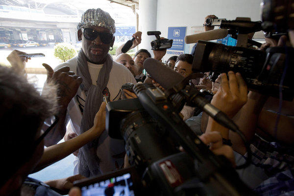 Retired NBA star Dennis Rodman, center, talks to journalists upon arriving Saturday at the Beijing airport.