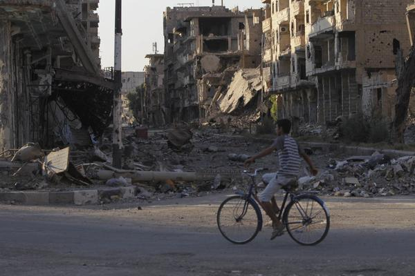 A boy rides his bicycle down a damaged street in Deir al-Zor, Syria. Two million Syrians reportedly are refugees.