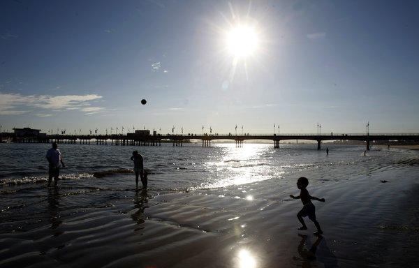 Jamie Jones, on the left, throws a ball to his son Jai in the Belmont Shore area of Long Beach. The Glendale family went to the beach to escape the heat.