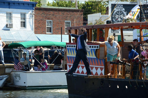 Annapolis Mayor Josh Cohen steps off of a tourist pirate ship and into the Annapolis harbor on Saturday morning, fulfilling a self-imposed punishment for not getting the city-owned Market House reopened by last fall. The market reopened on Labor Day weekend, with vendors offering falafel, gelato, seafood, sandwiches and smoothies.