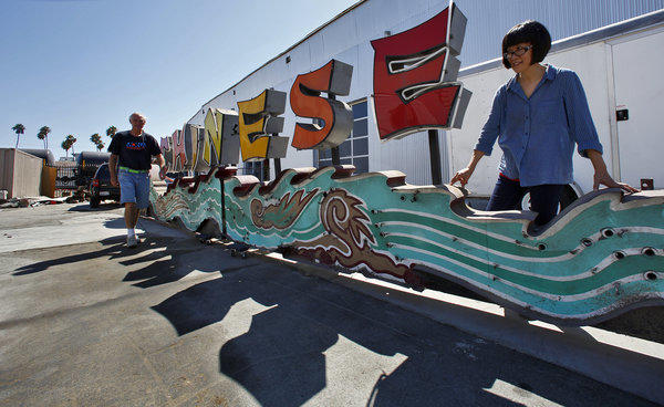 David Svenson and Kim Koga of the Museum of Neon Art survey a neon sign from Grauman's Chinese Theatre, which they're storing in a Pomona warehouse. They are trying to raise money to repair it.