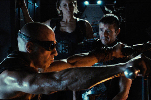 "From left to right: Riddick (Vin Diesel) is forced to work with Mercs Dahl (Katee Sackhoff) and Boss Johns (Matt Nable) in the movie ""Riddick."""