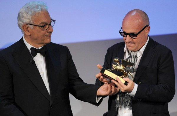 Italian director Gianfranco Rosi, right, receives the Golden Lion Award for the movie 'Sacro Gra' from Venice Biennale President Paolo Baratta.