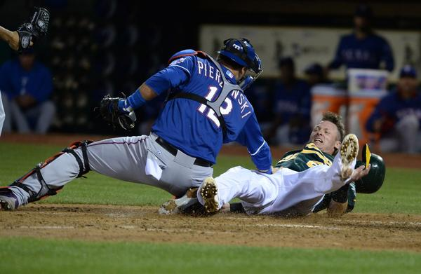 Oakland's Josh Donaldson is tagged out at home by Rangers' A.J. Pierzynski.