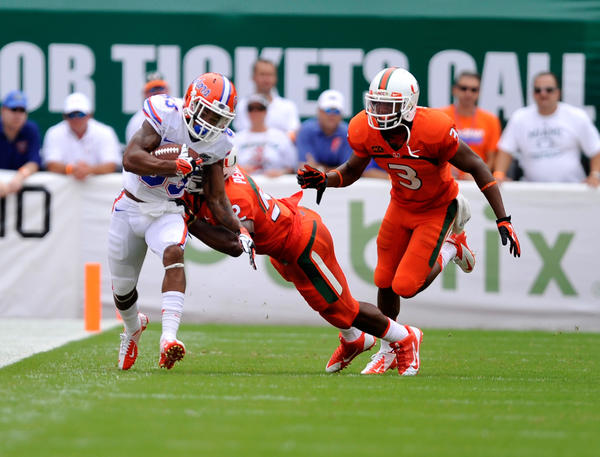 Florida Gators wide receiver Solomon Patton (83) is tackled by Miami Hurricanes linebacker Denzel Perryman (52) during the first half of the game at Sun Life Stadium.