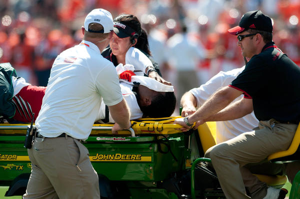 Cincinnati quarterback Munchie Legaux is carted off the field after an injury during the fourth quarter.