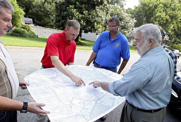 From left: James Clark, a Newport News city engineer; Matthew Roth, VIllage Green resident; Frank James, of the city's public works department; and Brian Lewis, chief of environmental engineering for the city, look at a map showing where storm water flowing from Village Green ends up.