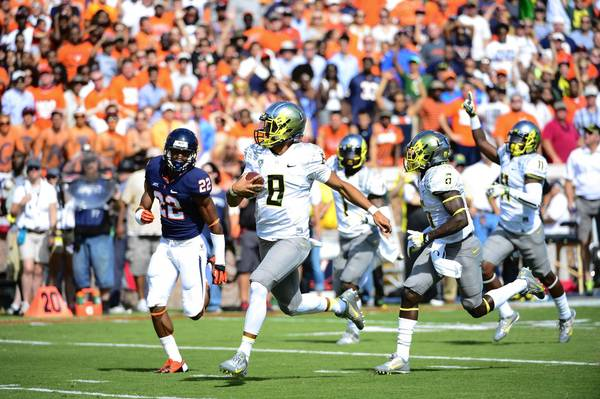 Bob Donnan/USA TODAY Sports Photo Oregon quarterback Marcus Mariota runs for a touchdown in the first few minutes of the first quarter as Virginia Cavaliers cornerback DreQuan Hoskey (22) defends at Scott Stadium. Mandatory Credit: