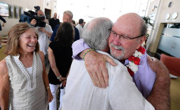 John Odom, right, gets a hug at Los Angeles International Airport. In April, shrapnel from the Boston Marathon bombings went through his left leg and into his right leg, puncturing a sciatic nerve and arteries, nearly killing him.