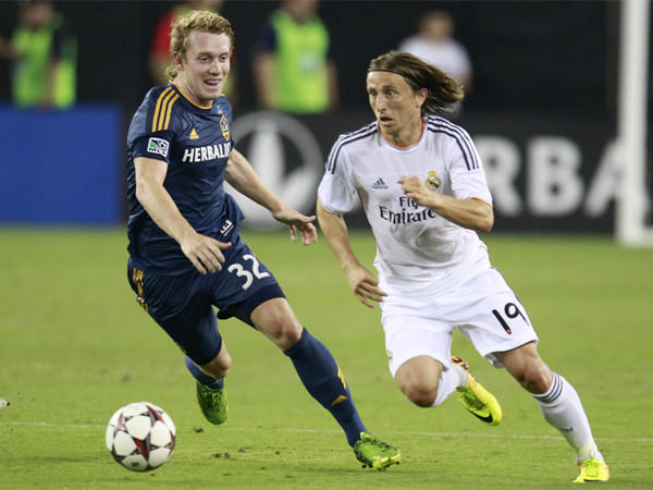 Galaxy forward Jack McBean, left, and Real Madrid midfielder Luca Modric chase a loose ball last month.