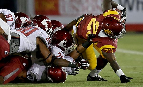 USC tailback Tre Madden is brought down by a pack of Washington State defenders Saturday at the Coliseum.
