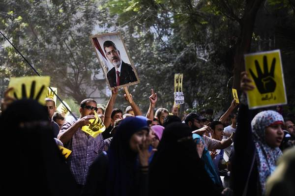 Members of the Muslim Brotherhood and supporters of ousted President Mohamed Morsi march through a Cairo neighborhood Friday.