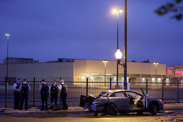Chicago Police officers stand near a car involved in a three-vehicle accident at the intersection of West Kostner and Grand Avenues Sunday, Sept. 8, 2013, in Chicago. A man in the car died from injuries sustained in the crash.