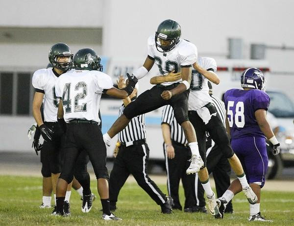 Oronde Crenshaw of Costa Mesa High (30) and Oliver Ferris celebrate recovering a fumble against Santiago on Saturday.