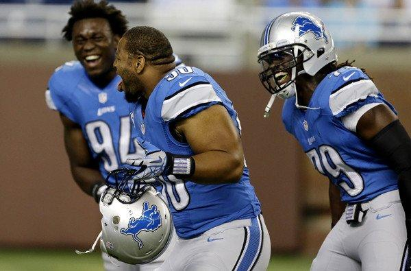 Detroit Lions defensive end Ezekiel Ansah (94), defensive tackle Ndamukong Suh (90) and defensive end Willie Young (79) share a laugh as they warm up for Sunday's game against the Vikings.