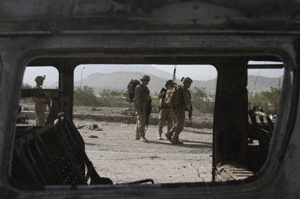U.S. troops, part of the NATO-led International Security Assistance Force, investigate the site of a suicide attack in Wardak province, east of Kabul, Afghanistan, on Sunday.