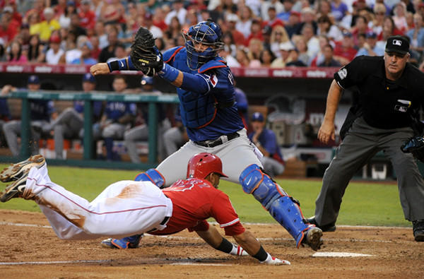 Angels third baseman Luis Jimenez dives toward home plate to score in the second inning ahead of a tag by Rangers catcher A.J. Pierzynski on Saturday night in Anaheim.