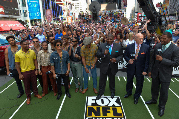 Bruno Mars, sixth from left, is with Curt Menefee, from third right, Terry Bradshaw and Michael Strahan in Times Square after it was announced Sunday that Mars will play during the Super Bowl XLVIII halftime show Feb. 2.