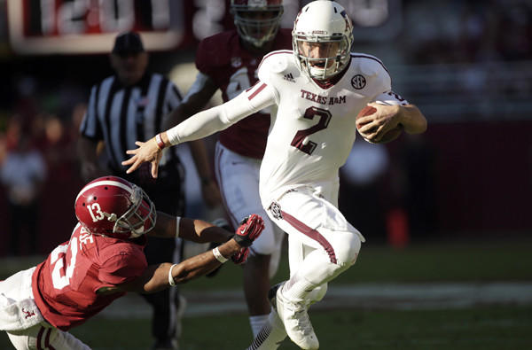 Texas A&M quarterback Johnny Manziel (2) evades the tackle attempt of Alabama defensive back Deion Belue (13) during their game last season.
