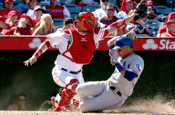 Rangers center fielder Leonys Martin slides safely past Angels catcher Hank Conger to score a run in the seventh inning Sunday afternoon in Anaheim.