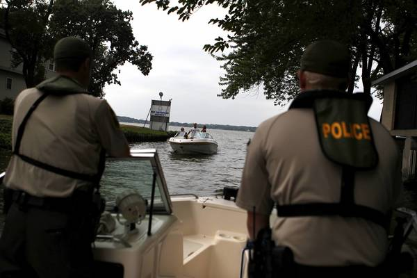 Illinois Department of Natural Resources police officers Jeff Kelle, left and Tom Davis monitor boaters on the Chain Of Lakes last year.