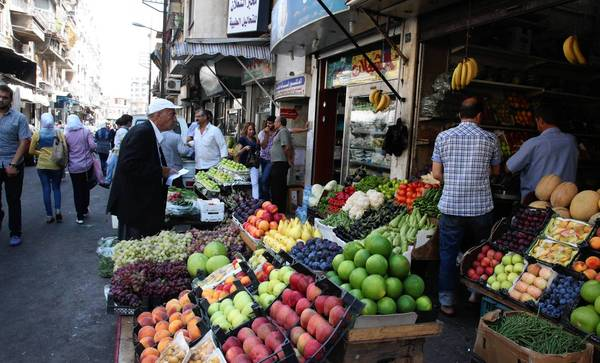"Syrians buy produce at a market in Damascus, the capital. ""Frankly, I hope they don't want to kill us because we didn't take up arms with them,"" one resident said about the rebels."